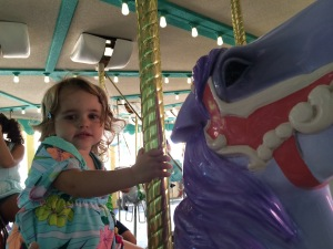 Rose picked out her favorite purple horse on the carousel.